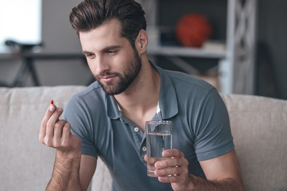 Young Man with a Pill and a Glass of Water in Hand